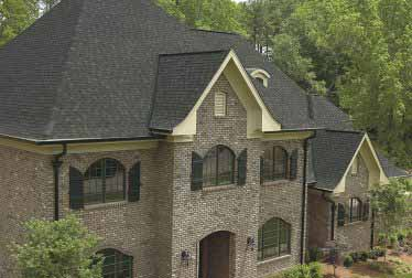 Big house in the woods with windows installed by windows and siding contractors