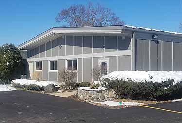 Big gray building with roof installed by roofing and siding contractor