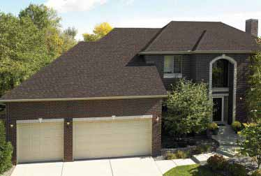 Big house with brick walls and garages with roof installed by roofing and siding contractors